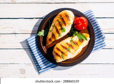Two delicious fresh grilled chicken breasts seasoned with herbs served on a plate with tomato on a white wood table, overhead view in summer sunshine
