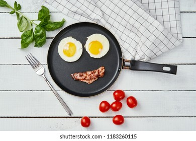 two delicious fried eggs and fried bacon arranged in a smiling face in a pan on a white kitchen table
