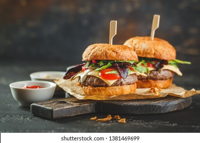 Two delicious homemade burger with beef, tomatoes, cheese, arugula and chard on a wooden cutting board. Street food, fast food.