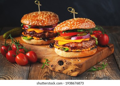 Two delicious homemade burgers of beef, cheese and vegetables on an old wooden table. Fat unhealthy food close-up.