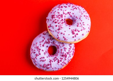 Two delicious lilac donuts with sprinkle on bright red background. Unhealthy, but tasty sweets. Copy space. Top view
