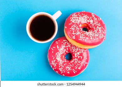 Two delicious pink donuts with sprinkle and cup of coffee on bright blue background. Unhealthy, but tasty sweets. Copy space. Top view