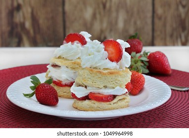 Two delicious strawberry shortcakes with whipped cream and garnished with a sliced berry.  Dessert  on a white plate with additional strawberries.  Close up with copy space.