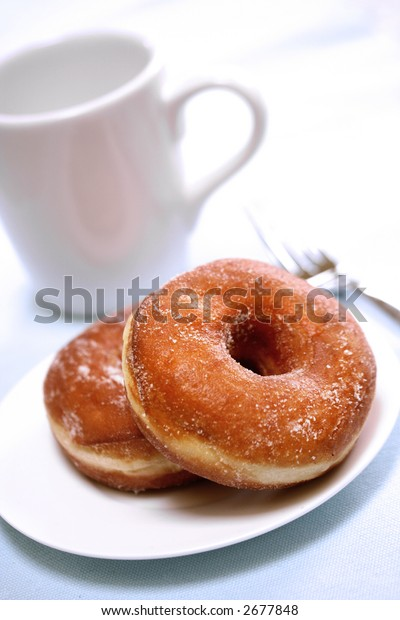Two delicious sugared ring donuts served on white plate with a cup of hot drink on the side.