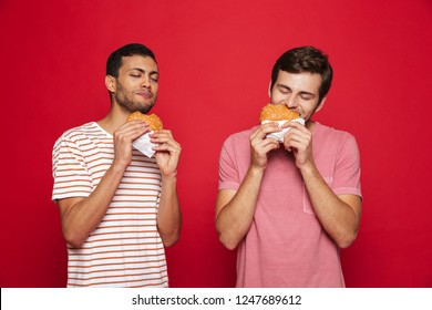 Two delighted men friends standing isolated over red background, eating burgers
