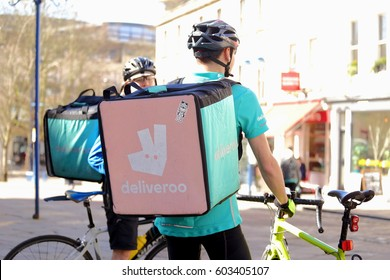 Two Deliveroo riders deliver takeaway foods in a box by bicycle in the street, Bath, Somerset,England,United Kingdom.The photo was taken on 13th of March, 2017.