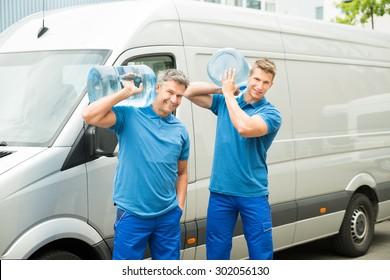 Two Delivery Men In Front Of Cargo Van Delivering Bottles Of Water