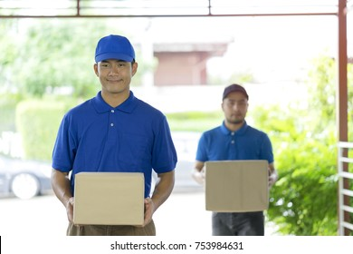 Two delivery men holding boxes and deliver to customer home (House). Smiling and standing in front of door and waiting customer to accept shipment from overseas. Door to door service delivery parcel.