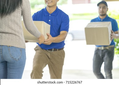 Two deliverymen holding boxes to delivery the parcel to receiver.Courier service deliver expedited shipment at home.Express service is taken few day to deliver package to recipient. Delivery concept.