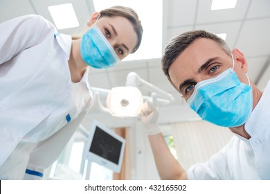 Two dentists making dental treatment to a patient in clinic
