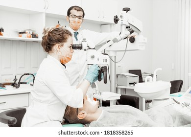 Two dentists treat a patient. Professional uniform and equipment of a dentist. Healthcare Equipping a doctor's workplace. Dentistry.