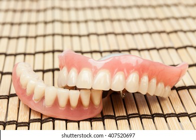 Two dentures on wooden mat