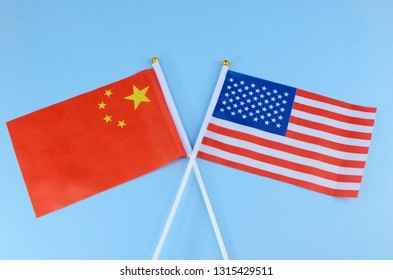 Two desktop flags on wooden desk with outdoor blue sky background. The flags are United States and China. Good image for trade talks or any other social, economic or political meetings between the two