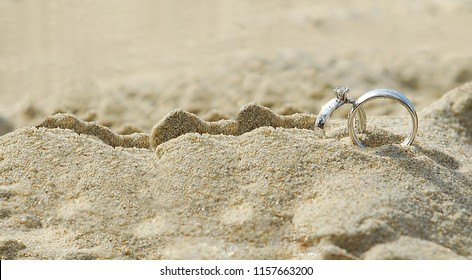 Two diamond rings on the sand. And they are wedding rings. backgrounds textures