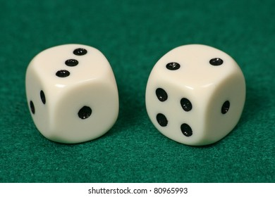 two dice on a green rug