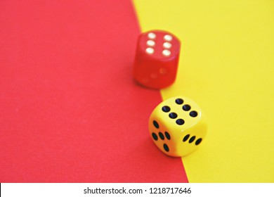Two dice with opposite color play - one dice is yellow and stands on red background, the other red on yellow background - concept with colors and dice