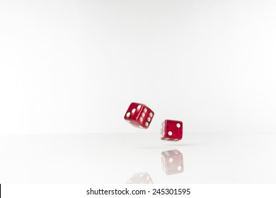 Two dice rolling along on white background with blur and movement