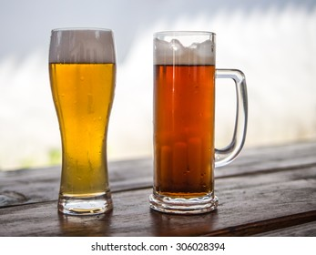 Two different beer drings in a beer mug and glass, light and dark, barley and wheat