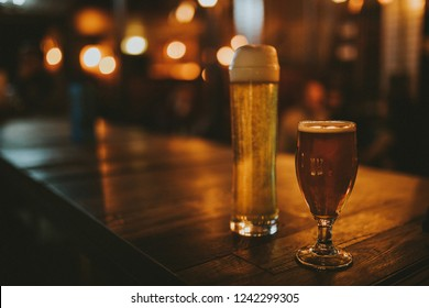 Two different beers on a wooden table, with pub lights in the background at night, and left copyspace.