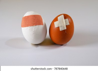 Two different color eggs with problems, injuries pasted with medical plaster