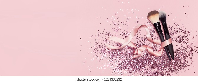 Two different Cosmetic makeup brushes with pink ribbon and holographic glitter confetti in the form of stars on pink background Flat lay top view copy space Makeup accessories holiday birthday newyear