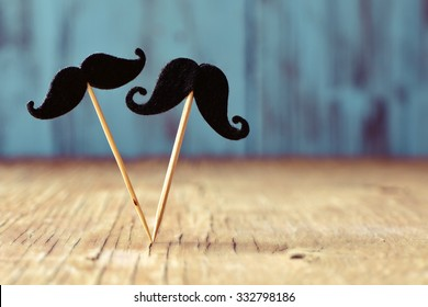 two different felt mustaches in sticks on a rustic wooden surface