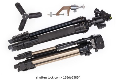 Two different folded photographic tripods with ball and pan-tilt heads, tabletop mini tripod and old vintage camera mount bracket on a white background, top view