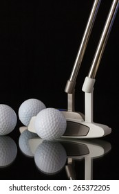 Two different golf putters and three balls on a black glass desk