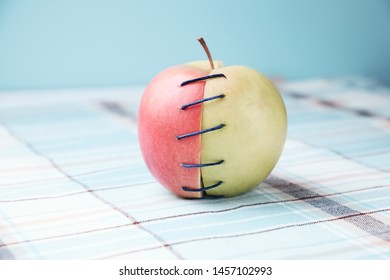 Two different halves of apple connected by thread