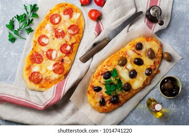 Two different oval Greek pizza with olives and tomato Margarita on gray concrete background. Selective focus. Top view. Copy space.