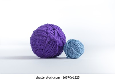 Two different sized yarn balls next to each other on a gray surface and white background.  Large purple ball next to small light blue ball.  Macro shot of colored yarn balls.