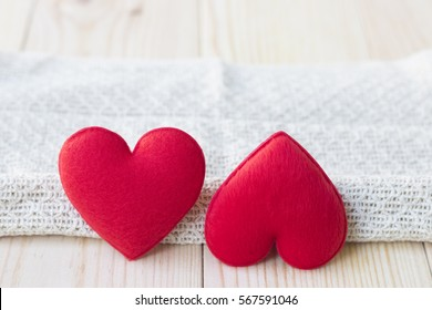 Two different valentine's heart on wooden table background. With copy space. Marital difficulties concept.