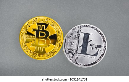 Two digital coins are golden Bitcoin and silver Lightcoin. View from top.