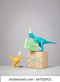 Two dinosaurs with Party hats and birthday presents on a light grey background.