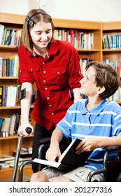 Two disabled students, one in a wheelchair, one on hand crutches, in the school library.