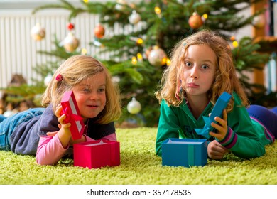 two disappointed girls with presents in front of christmas tree