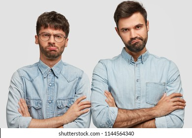 Two displeased guys keep arms folded, look with sullen expression, feel like loosers after loosing game, dressed in fashionable denim clothes, stand next to each other over white background.
