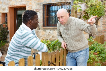 Two displeased male neighbors talking through wooden fence