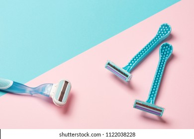 two disposable blue razors and one reusable on pink background. copy space, top view