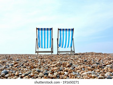 Two distant deck chairs on a pebble beach, looking out towards the horizon.