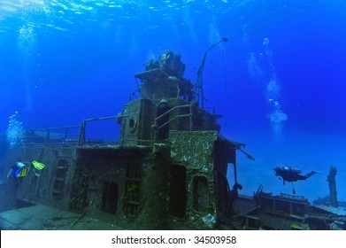 Two divers are exploring the superstructure of the sunken wreck, the Tibbetts, a Russian frigate that was sunk in the waters off Cayman Brac.