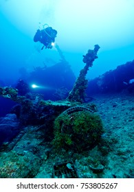 Two divers with torches approach an anti-tank gun on the deck of the WWII wreck of the Nippo Maru, at Truk Lagoon, Micronesia.