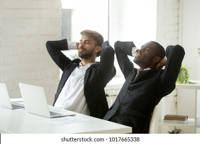 Two diverse businessmen relaxing after work breathing fresh air, relaxed african and caucasian partners in suits resting at workplace, executive corporate team enjoying break meditating in office