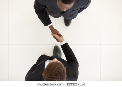 Two diverse businessmen shaking hands in office, black and white partners greeting with handshake as respect concept, collaboration deal, support, business acquaintance, first impression, top view