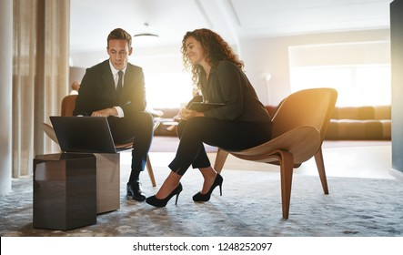 Two diverse businesspeople talking and working together on a laptop while sitting in a bright modern office