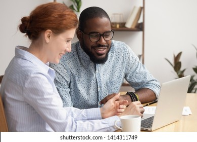 Two diverse laughing businesspeople watching funny video on laptop having coffee break at work. Friendly colleagues talking working together joking satisfied with teamwork, good news and results