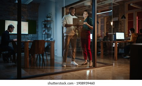 Two Diverse Multiethnic Colleagues Have a Conversation in a Meeting Room Behind Glass Walls in an Agency. Female Creative Director and African American Project Manager Discuss Work on Laptop Computer.