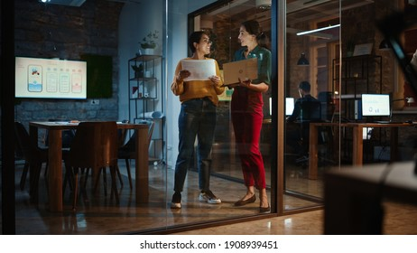 Two Diverse Multiethnic Female Have a Discussion in Meeting Room Behind Glass Walls in an Agency. Creative Director and Project Manager Compare Business Results on Laptop and App Designs in an Office.