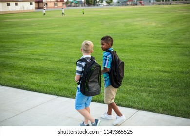 Two diverse school kids walking and talking together on the way to school. Back to school photo of diverse school children wearing backpacks