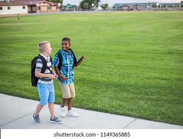 Two diverse school kids walking home together after school and talking together. Back to school photo of diverse school children wearing backpacks